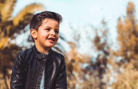 Fashion little boy wearing a leather jacket. Park or forest, outdoor Фото со стока