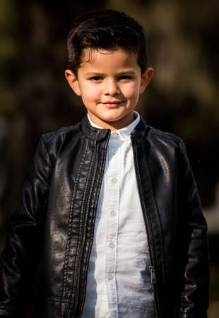 Fashion little boy wearing a leather jacket. Park or forest, outdoor Stockfoto