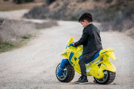 A happy little boy driving a toy motorcycle, dressed in a leather biker jacket on a country road Stock Photo