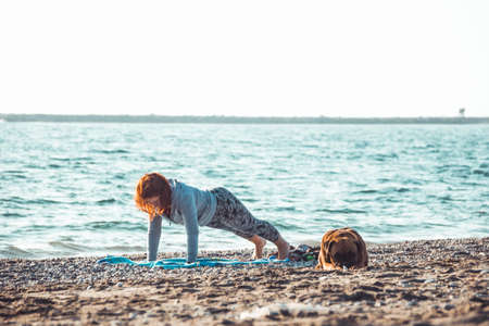 young woman doing yoga and stretching on the beach with her dog 스톡 콘텐츠