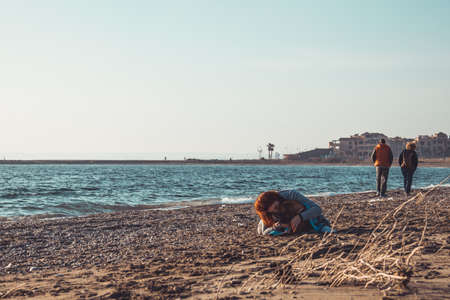 redhead girl hugging and drying her dog on the beach. Punta Entina en Almerimar, Almeria, Andalusia, Spain