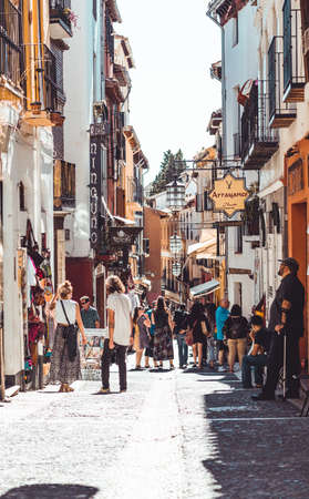 Granada, Spain - June 15, 2019: typical restaurants and shops in a street of the popular old Moorish quarter Albaicin. The historical center of Granada Town. Caldeleria street