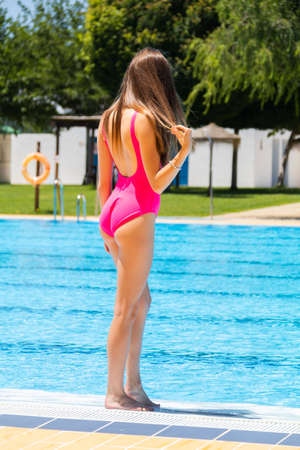 Girl with swimsuit posing on a swimming pool