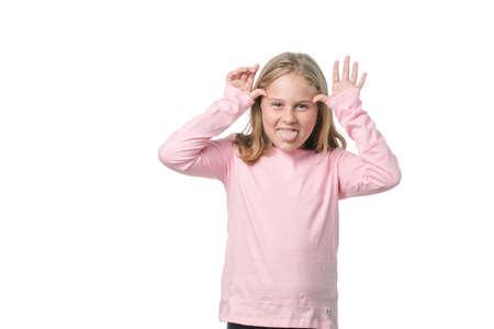Lustiges kleines Mädchen, das der Kamera die Zunge auf weißem Hintergrund zeigt