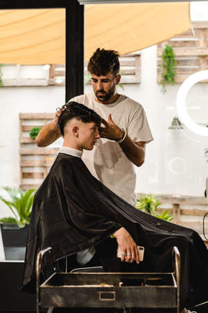 Men Hair Salon. Barber Doing Haircut In Barbershop. Young Male Client And Hairdresser. Zdjęcie Seryjne