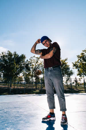 Young cool man break dancer standing in park. Tattoo on body Stock Photo