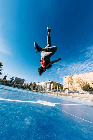 Parkour man doing tricks on the street - Free runner training his acrobatic port outdoors Фото со стока - 134845583