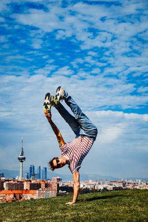 B-boy performing some moves. Breakdancer in modern city background