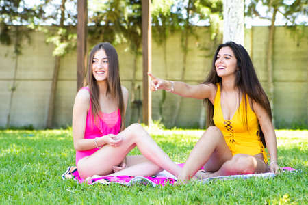Two young girls in bathing suits sitting on the pool lawn and pointing at something