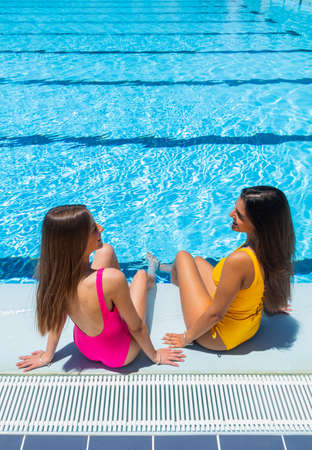 two teenagers in swimsuits in a pool