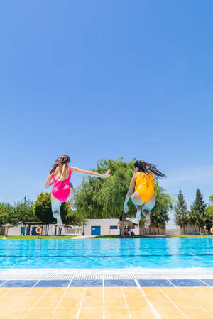 Two young girls jumping into the pool. Summer begins concept. Copy space