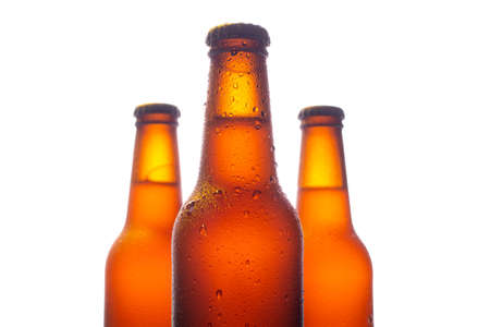 Three fresh beer bottle with big water drops on white background