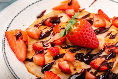 Pancakes with fresh strawberry on a blue wooden background