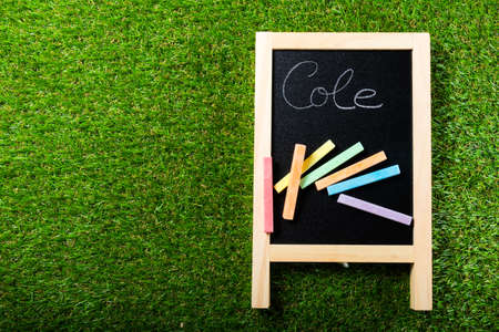 Top view of mini blackboard and colors on plastic grass background. Concept back to school. Cole is School in spanish Standard-Bild