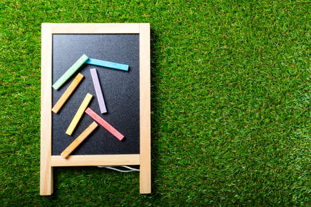 Top view of mini blackboard and colors on plastic grass background. Concept back to school Standard-Bild