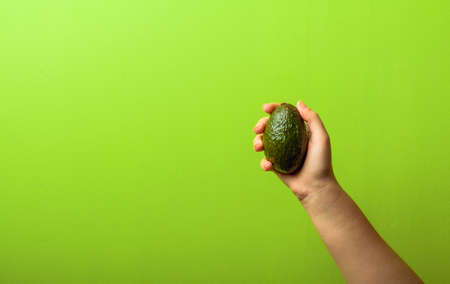 avocado in a hand of woman green background. healthy food concept