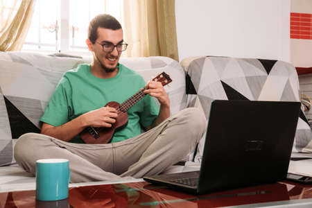 Young man learning to play the ukulele online from his couch