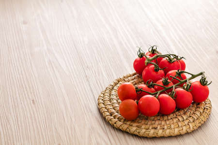 Small red cherry tomatoes on rustic background Standard-Bild