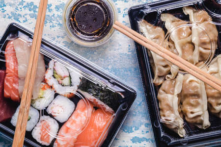 Sushi to go concept. Takeaway box with assorted sushi and gyoza Foto de archivo
