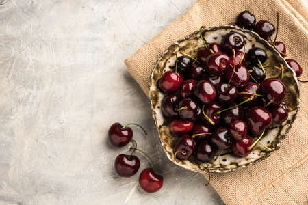 Ripe sweet cherry in ceramic bowl at concrete background