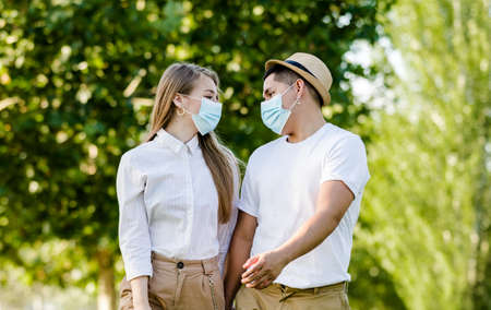 Couple with protective mask walking in the park