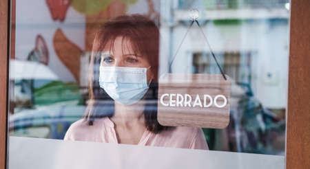 sad woman with face mask changing open to closed sign in spanish on window for virus