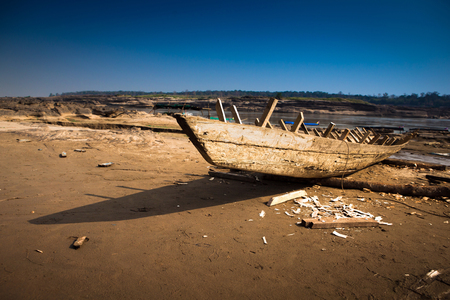 tumble down: old broken boat on the sand Stock Photo