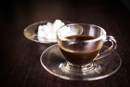 sugar cube: a cup of coffee in front of a blurry plate of sugar cube