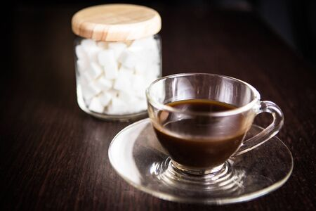 sugar cube: a cup of coffee in front of a blurry  jar of sugar cube