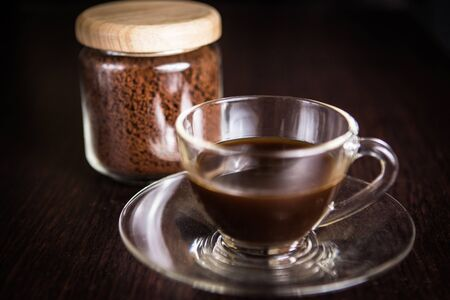 crush: a cup of coffee in front of a blurry  jar of crush coffee bean Stock Photo