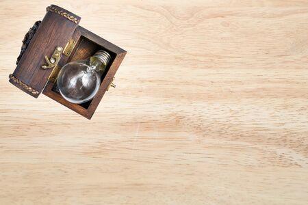box: light bulb in the wood chest on the wood background