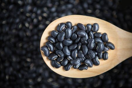 black bean: black bean in a scoop on the blurry black bean background. Selective focus. Stock Photo