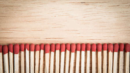 ignite: pile of match arrange in a row on a wood background