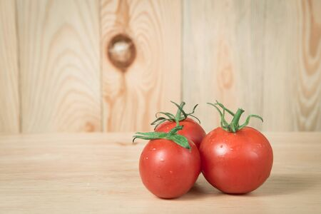 lycopene: three tomatoes on a wooden block in front of a blurry wooden  background