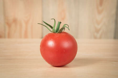 lycopene: tomato on a wooden block in front of a blurry wooden  background