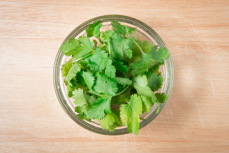 bowl of  coriander leaf on a wooden block