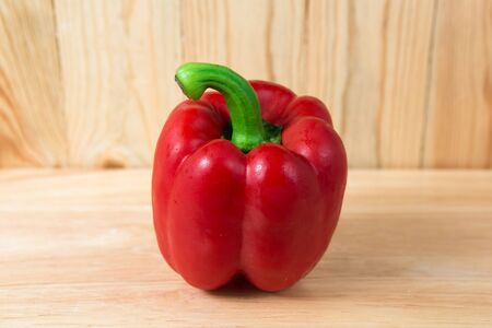 red sweet pepper on a wooden block Stock Photo