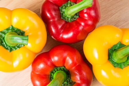 group of red and yellow sweet pepper on a wooden block