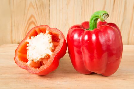 red sweet pepper and a half on a wooden block