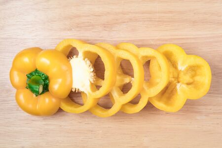 sliced yellow sweet pepper on a wooden block