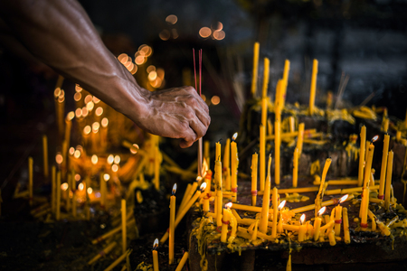 A hand of a man try to ignite an incense with a candle