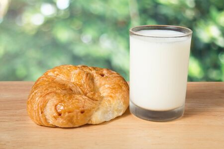 butter croissant and a glass of milk on a wooden block