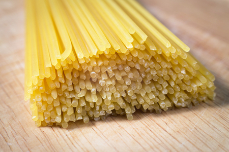pile of raw spaghetti on a wooden block Stock Photo