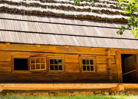 Old nice wooden house with open window and thatched roof in village summer warm day Stock Photo