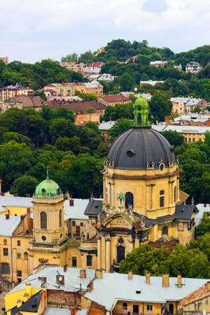 lvov: Top view house roof and Cathedral of old European city Lvov in Ukraine under cloudy blue sky