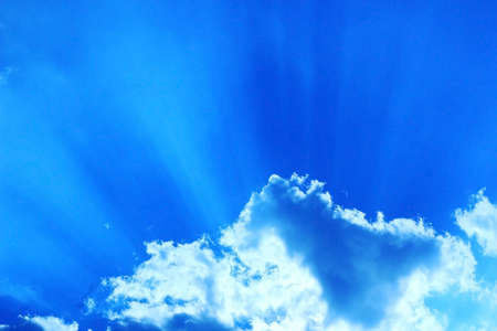 Dark blue sky with white clouds from which suns rays make their way background Stock Photo