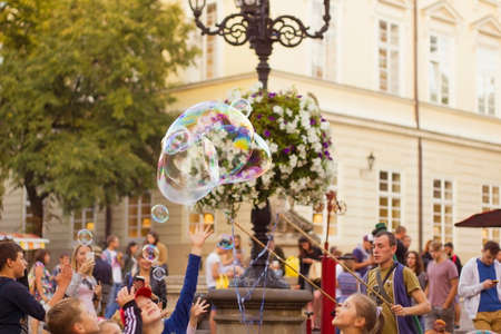 lvov: Man inflates big soap bubbles on Market Square in Lvov. Wiev of city life