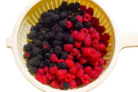 Fresh raspberries and blackberries in sieve isolated on white background