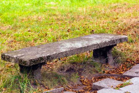Old stone bench in autumn park Stock Photo