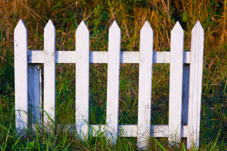 Low white small wooden fence in grass Stock Photo